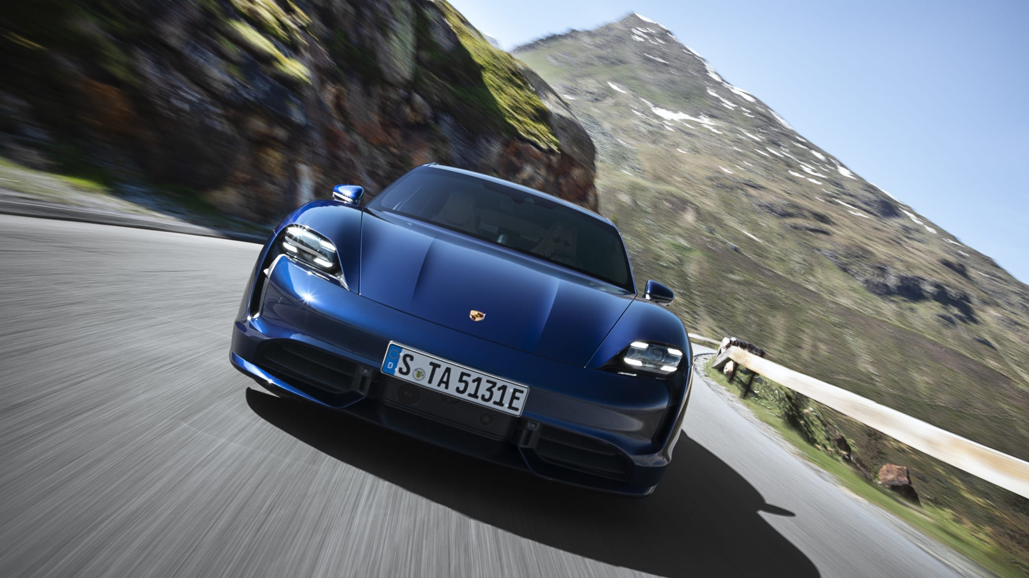 auf Landstrasse fahrender Porsche Taycan