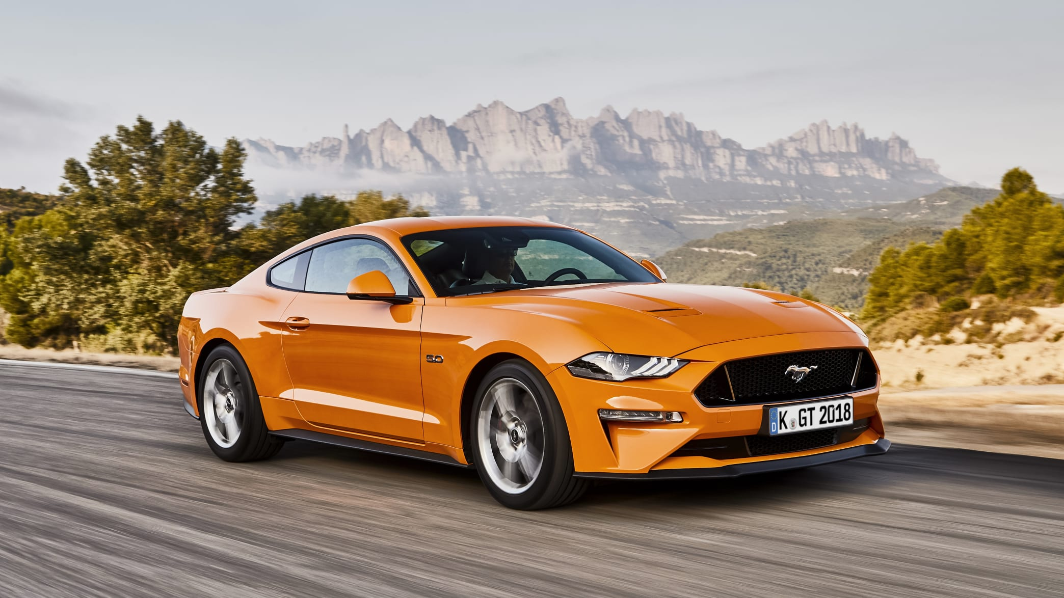 Orangener Ford Mustang Sportwagen fahrend