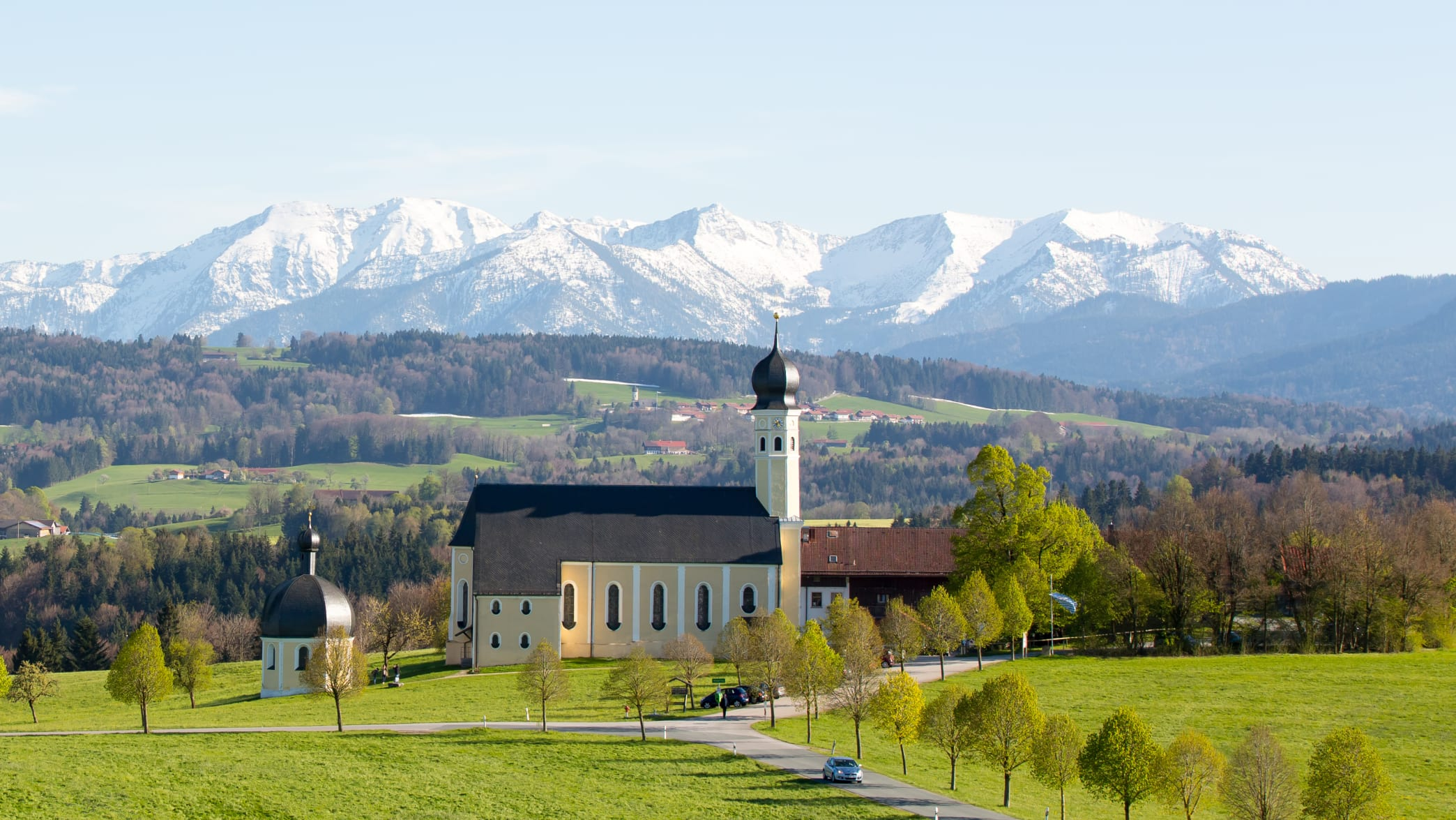 Die Wallfahrtskirche Wilparting vor der verschneiten Bergkulisse