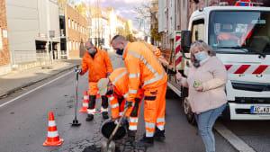 Straßenarbeiter verfüllen ein Schlagloch