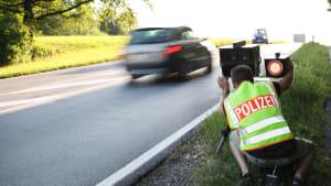 Polizist bedient Blitzgerät an einer befahrenen Strasse