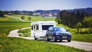 BMW mit Wohnanhänger fährt auf Landstraße