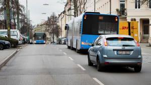 Ein Auto steht hinter einem Bus auf einer Strasse