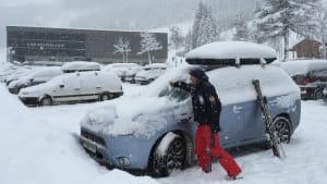 Mann befreit Auto von Schnee im Winter