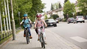 Zwei Kinder fahren mit ihren Fahrrädern auf dem Bürgersteig.