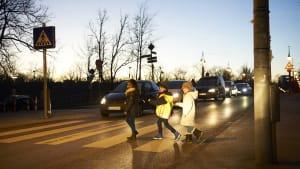 Kinder gehen bei Dämmerung über einen Zebrastreifen