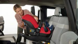 Junge Mutter befestigt den Kindersitz ihres Babys auf der Rückbank des Autos vorschriftsmäßig