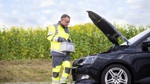 Ein Pannenhelfer vom ADAC trägt eine Autobatterie zu einem Wagen.