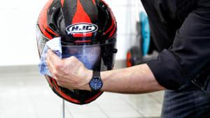 Das Visier eines Motorradhelms wird gereinigt
