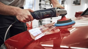 Ein Mann poliert mit einem Poliergerät die Motorhaube eines roten Autos