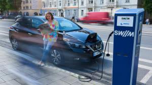 Frau lädt ihr Elektroauto an einer Ladesäule in München