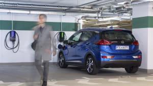 Ein Mann geht in einer Tiefgarage, im Hintergrund steht ein Elektroauto.