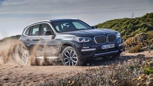 BMW X3 fahrend auf einem sandigen Weg