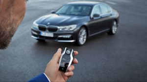 Mann hält einen Autoschlüssel von BMW in der Hand. Im Hintergrund steht ein 7er BMW