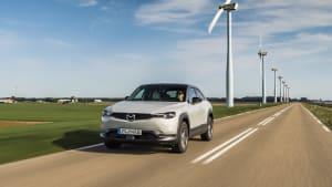 Mazda MX 30 fährt an einer Windanlage vorbei