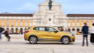 goldener BMW X2 faehrt an Gebaude vorbei