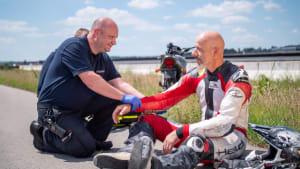 Ein Feuerwehrmann kniet neben einem verletzten Motorradfahrer auf der Straße.