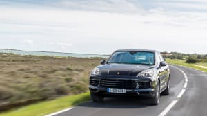 schwarzer Porsche Cayenne E-Hybrid faehrt auf Strasse