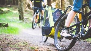 fröhlich lachendes Kind im Fahrradanhänger eines Mountainbikes bei einer fahrt durch den Wald