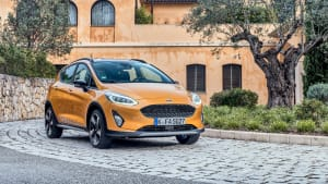 Goldener Ford Fiesta Active steht vor Gebaeude