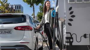Eine Fau tankt ihr Elektroauto an einer Ladesäule auf