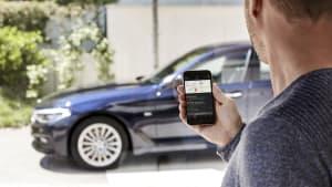 Mann verbindet sein Smartphone mit parkendem schwarzen BMW