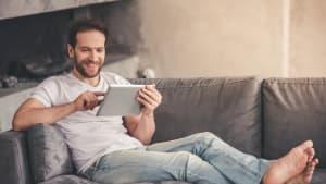 Ein Mann liegt auf dem Sofa mit einem Tablet in der Hand