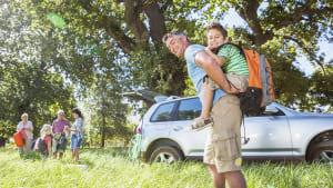 Familie vor SUV im Grünen