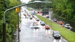Autos fahren auf einer nach einem Unwetter überschwemmten Straße in Berlin