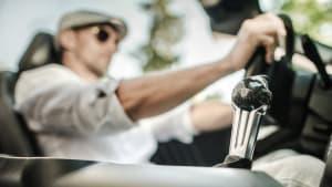 Mann mit Schirmmütze fährt in einem Cabrio