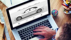 Ein Mann sitzt an einem Laptop mit einer Tasse Kaffee in der Hand und schaut auf ein Auto auf dem Bildschirm.