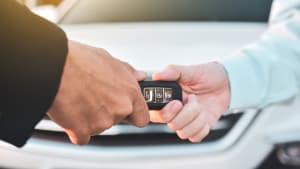 Verkäufer übergibt Käufer den Autoschlüssel