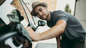 Ein Mann poliert sein Auto mit einem Lappen
