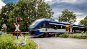 Zug fährt über Bahnübergang