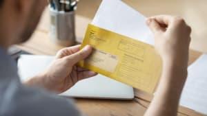 Ein Mann hat einen Bußgeldbescheid bekommen und öffnet gerade diesen gelben Brief