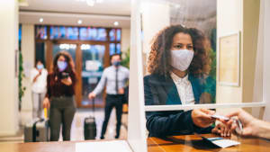 Frau mit Maske steht an einer Hotelrezeption
