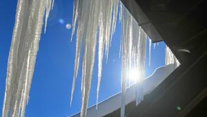 Lange Eiszapfen an einem Häuserdach glänzen im Sonnenlicht