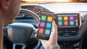Mann verbindet sein Smartphone mit den Apps auf seinem Autodisplay