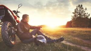 Motorradfahrer sitzt auf einer Wiese, angelehnt an sein Motorrad schaut er in den Sonnenuntergang