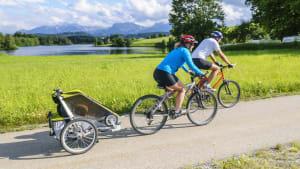 Zwei Fahrradfahrer fahren mit Anhänger durch die Landschaft