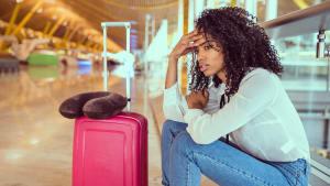 Frau sitzt mit ihrem Koffer am Flughafen