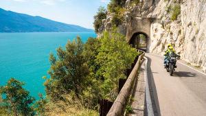Ein Motorradfahrer mit Sozius fährt am Gardasee vorbei