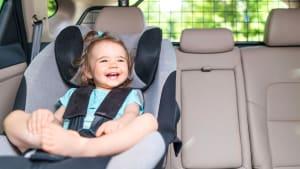 Baby sitzt im Kindersitz im Auto und lacht