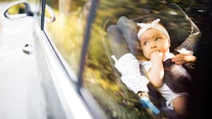 ein Baby sitzt in einem Kindersitz und nuckelt an den Fingern