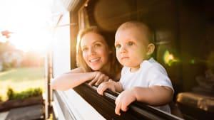 Frau guckt mit ihrem Baby aus dem Wohnwagenfenster