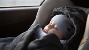 Baby schläft in einem Schlafsack in seinem Kindersitz