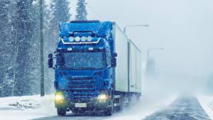 LKW fährt auf schneebedeckter Straße