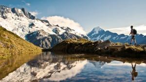 Ein Wanderer läuft an einem See vorbei, im Hintergrund sieht man schneebedeckte Berge.
