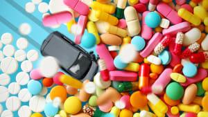Ein Spielzeugauto fährt in einen Haufen von Bunten Tabletten