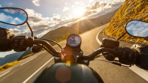 Ein Motorradfahrer fährt auf einer Straße durch eine bergige Landschaft